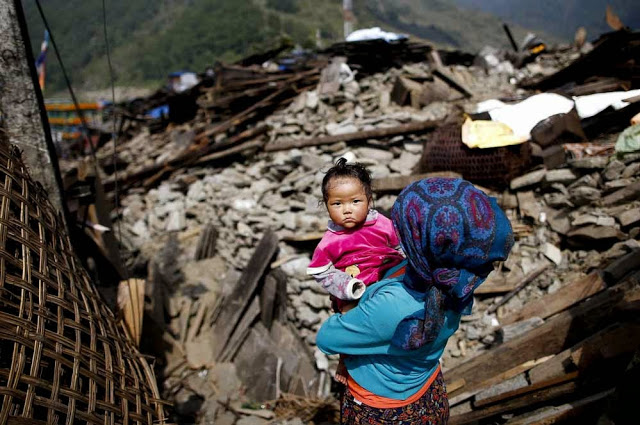 Mother holding a baby overlooking their destroyed home